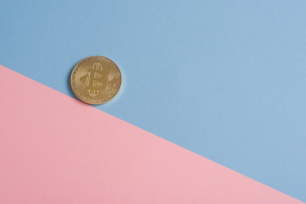 Bitcoin coin on blue and pink background