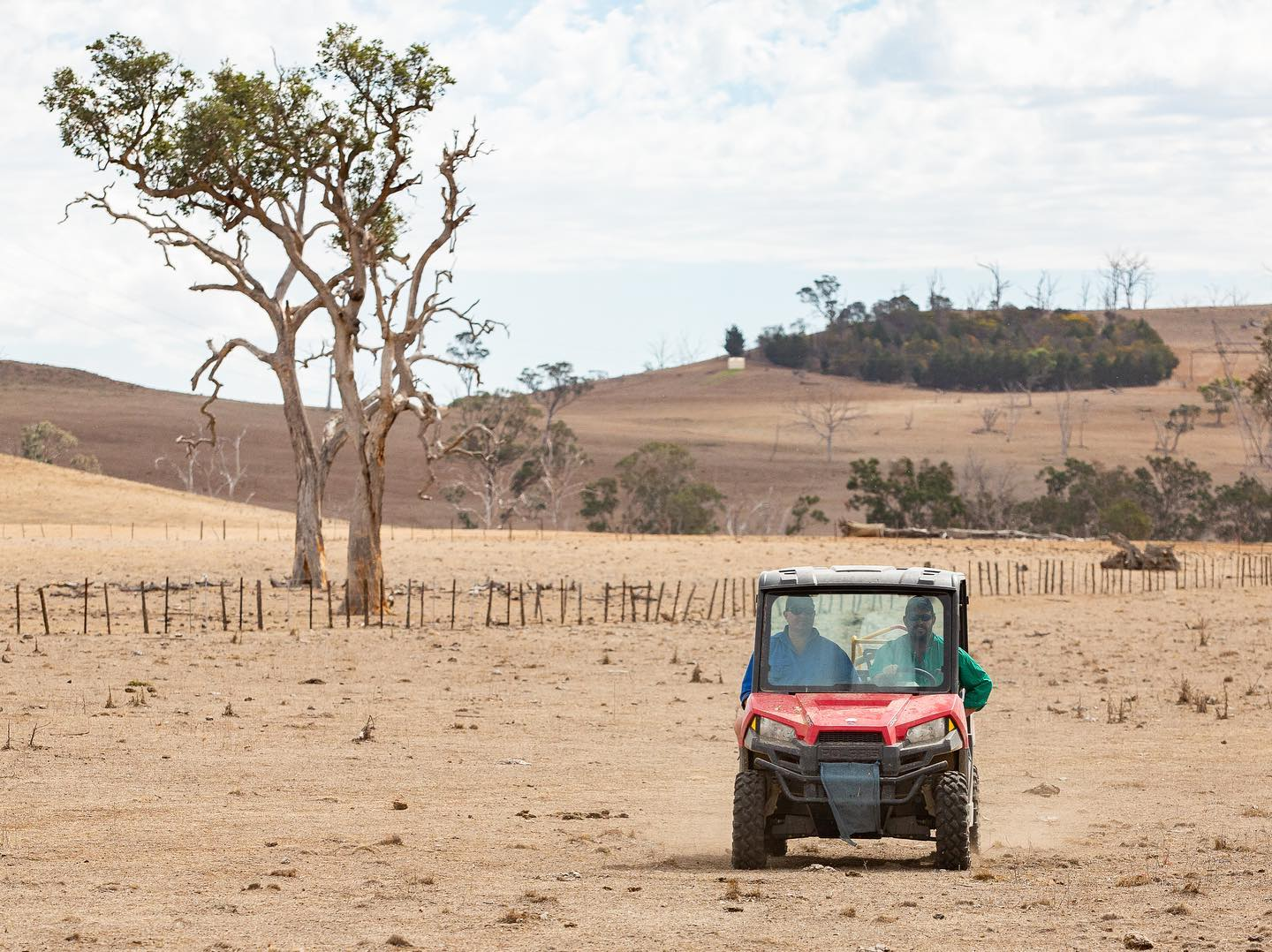 Farmers driving a 4 wheeler on a drought riddled farm - SimonScottPhoto