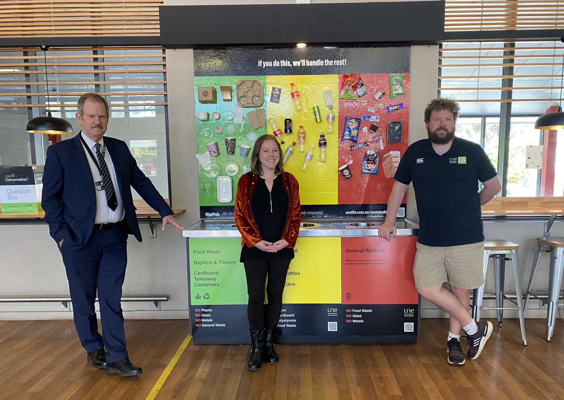 Peter Creamer, Suzannah Mitchell and Scot Leven standing in front of the Waste Wall at UNE Life's Cafe Life, UNE