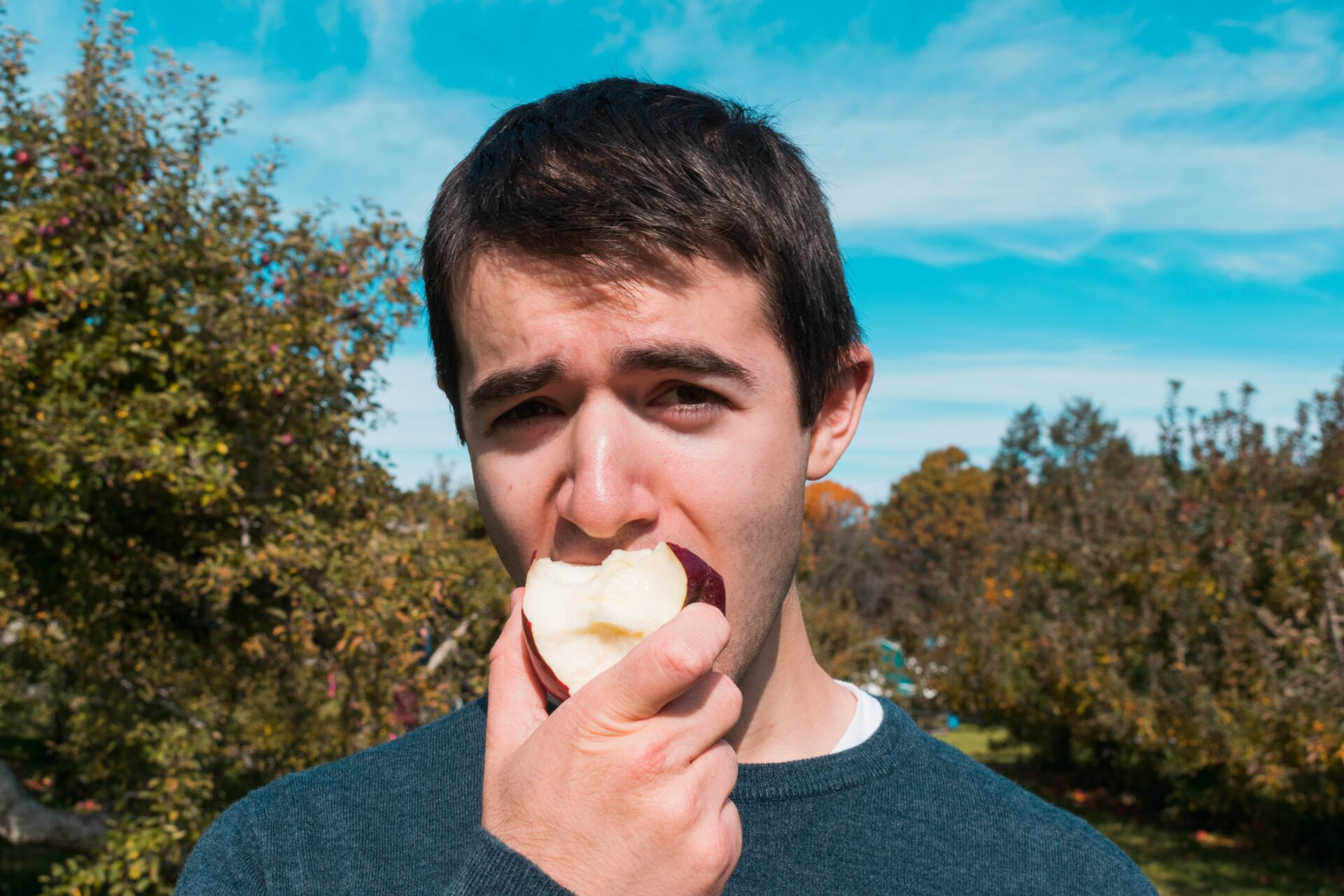 male student biting an apple with the blue sky behind him