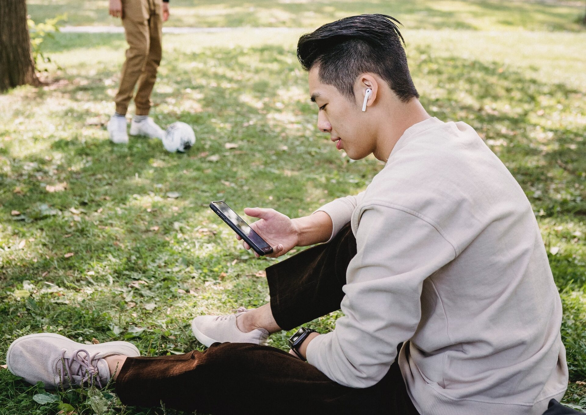young man sitting on the grass looking at his phone