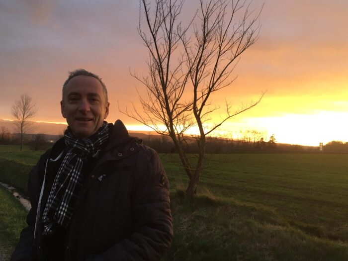 Anthony Wesley, UNE Alumni standing with a beautiful sunset behind him