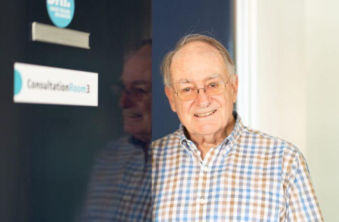 Geoff Quinn, UNE Alumni standing by a door