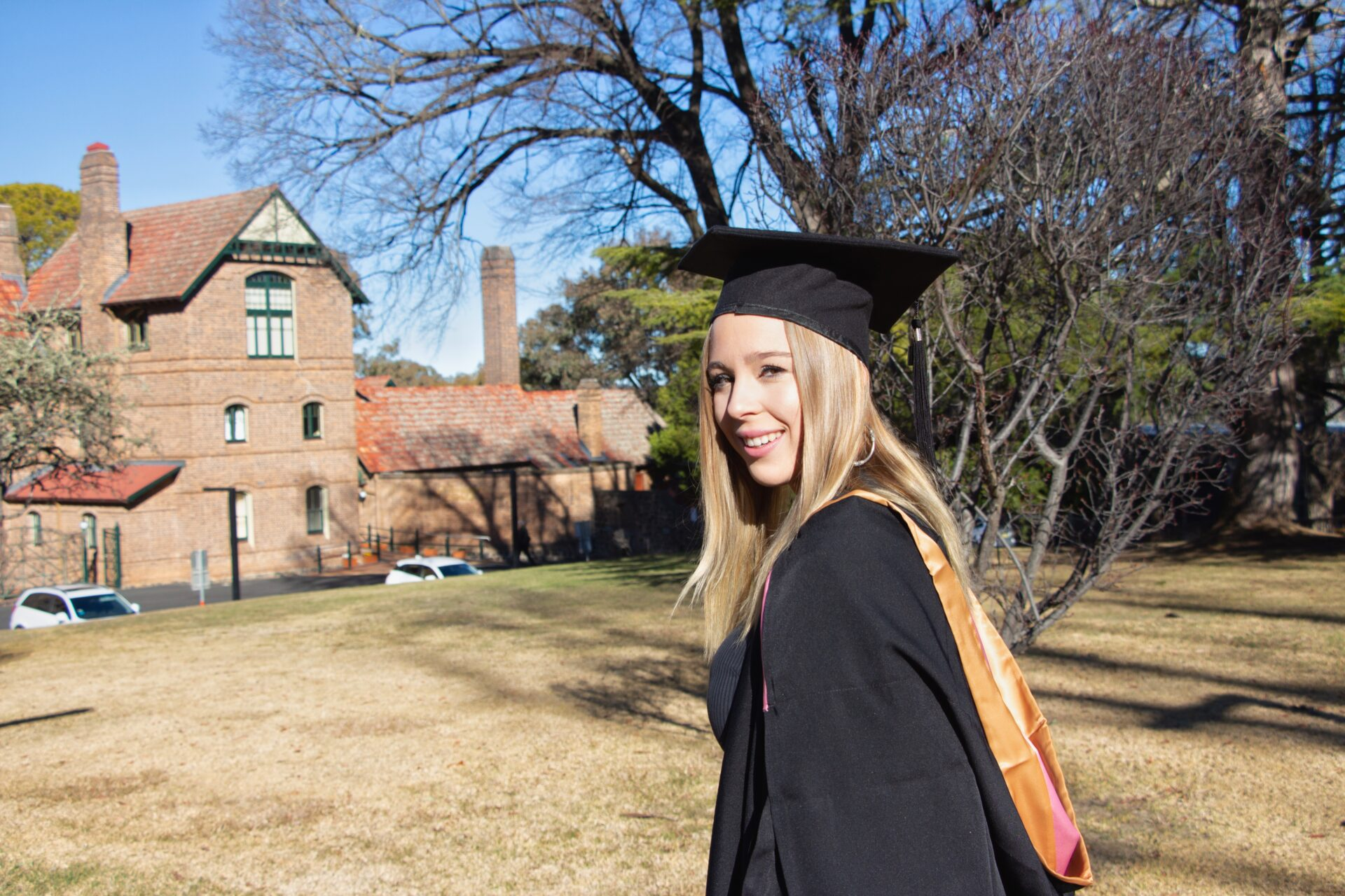 Blonde girl stands in front of UNE Booloominbah wearing graduation trencher hat and gown