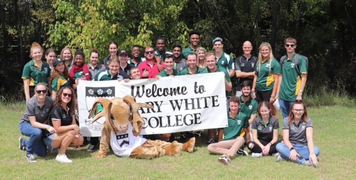 Photo of students from Mary White College holding a welcome sign