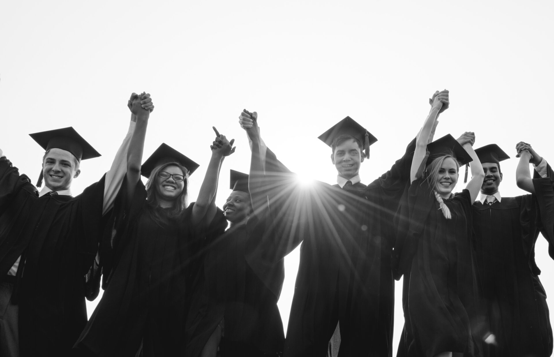 Black and white image of graduation students holding hands and smiling in their graduation gowns