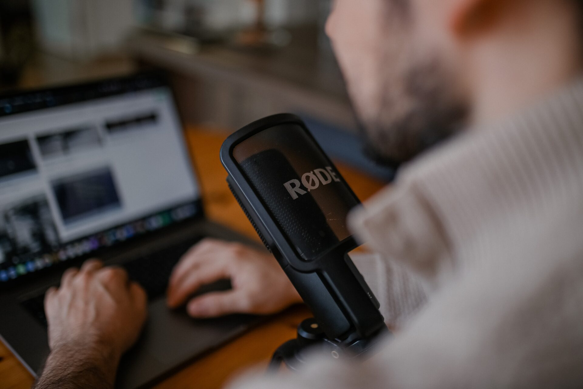 close up of a man recording a podcast, looking over his shoulder at the laptop and microphone