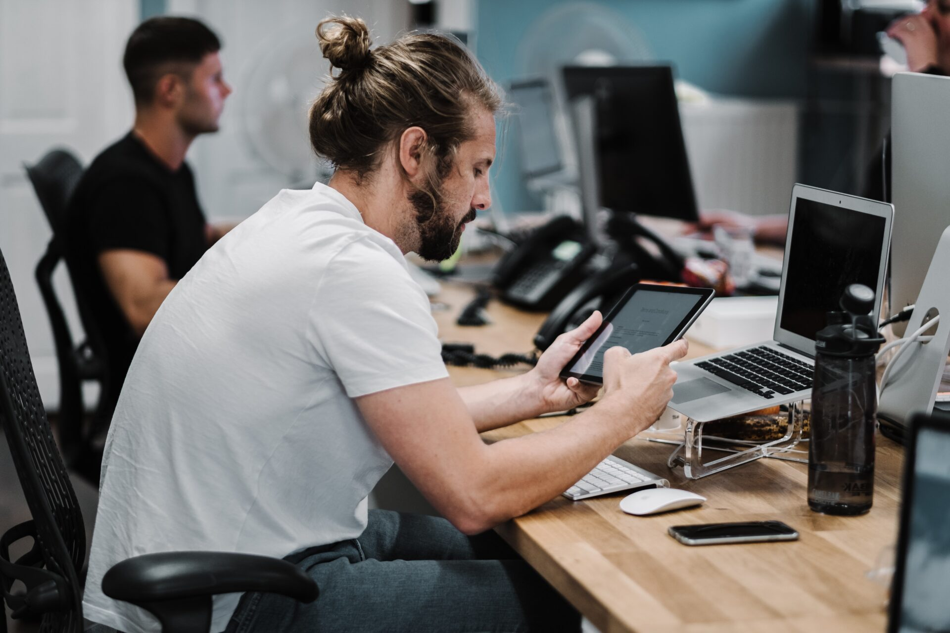 Man in a white shirt and jeans with a man bun, sitting at a computer looking stressed