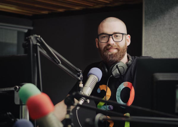 Tune!FM broadcaster Jacob Hunt sits in the studio with a microphone in front of him, smiling at the camera