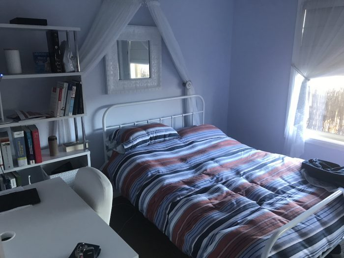 University student bedroom, with bookshelf and bed