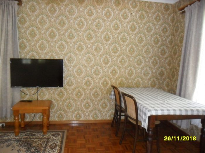 Room in the golden elm flat, with a tv and dining table