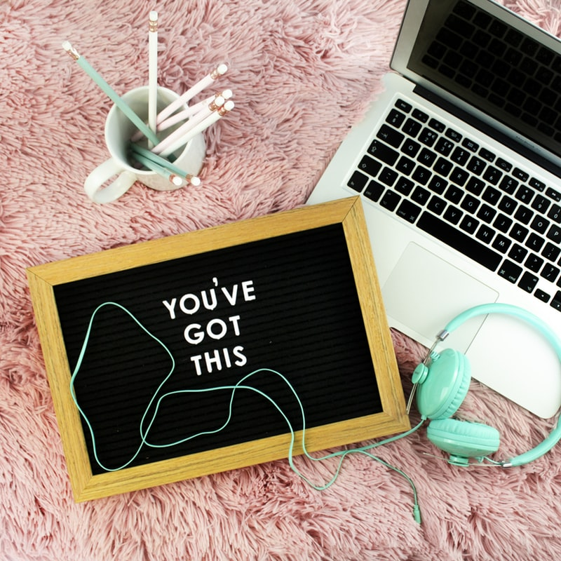A laptop, pens, headphones and letter board on a pink fluffy blanket.