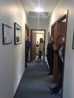 CAPS staff members looking out of their office doors, into the adjoining hallway