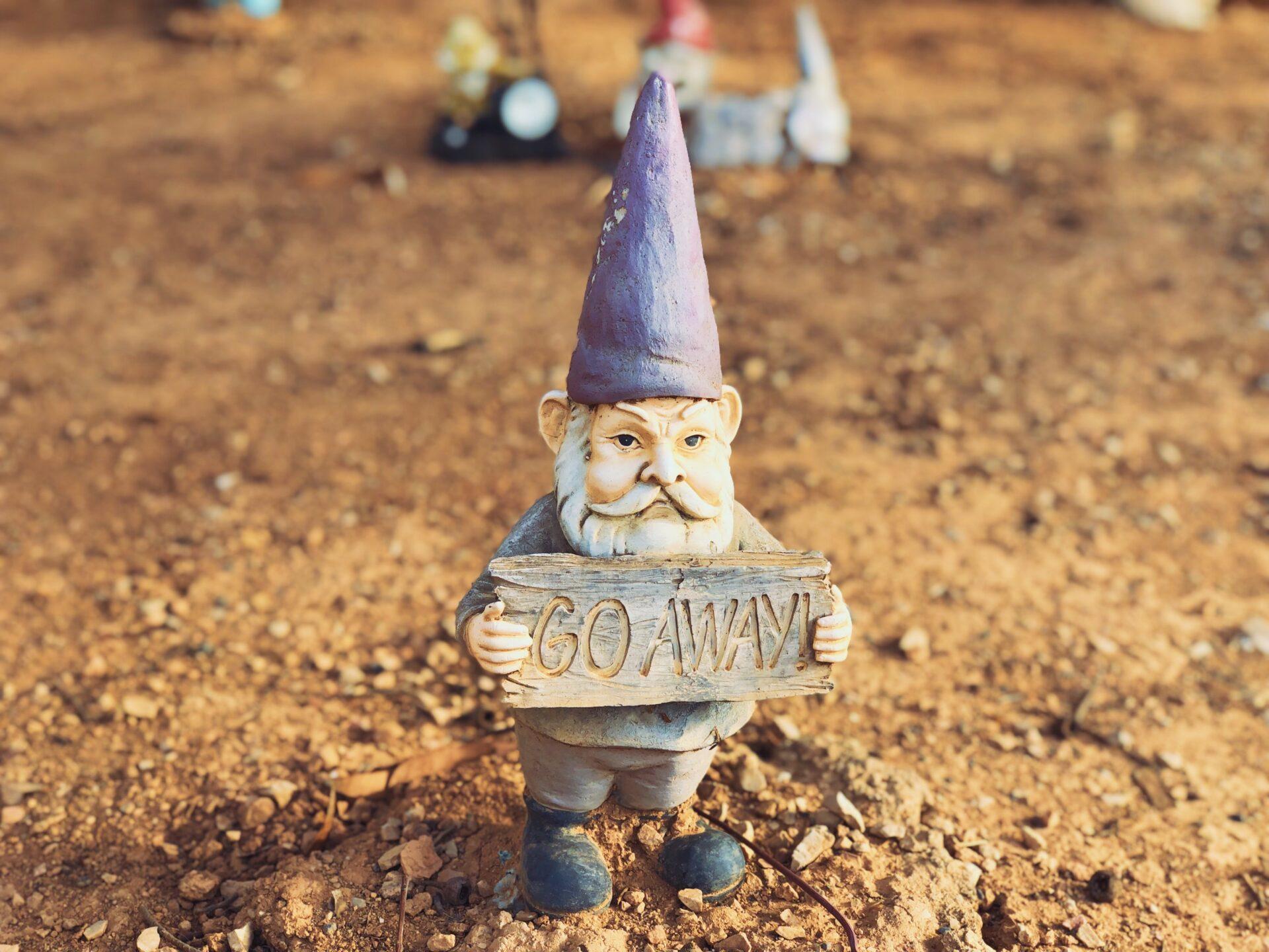 Garden gnome with a go away sign