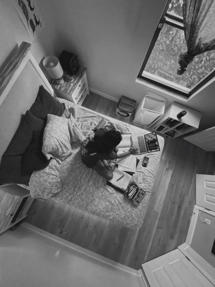 girl sitting on a bed viewing computer in black and white