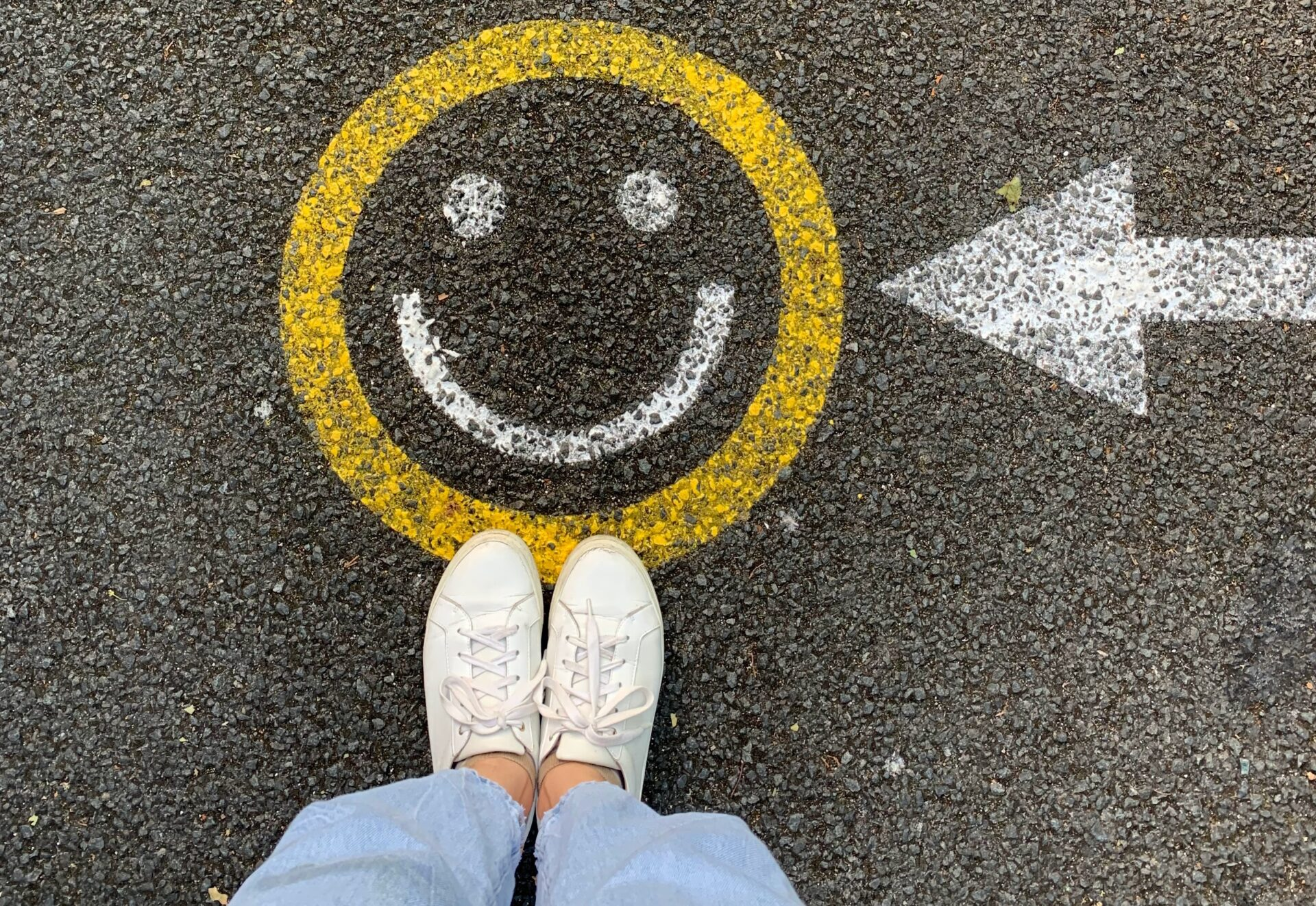 feet and a smily face painted on the road