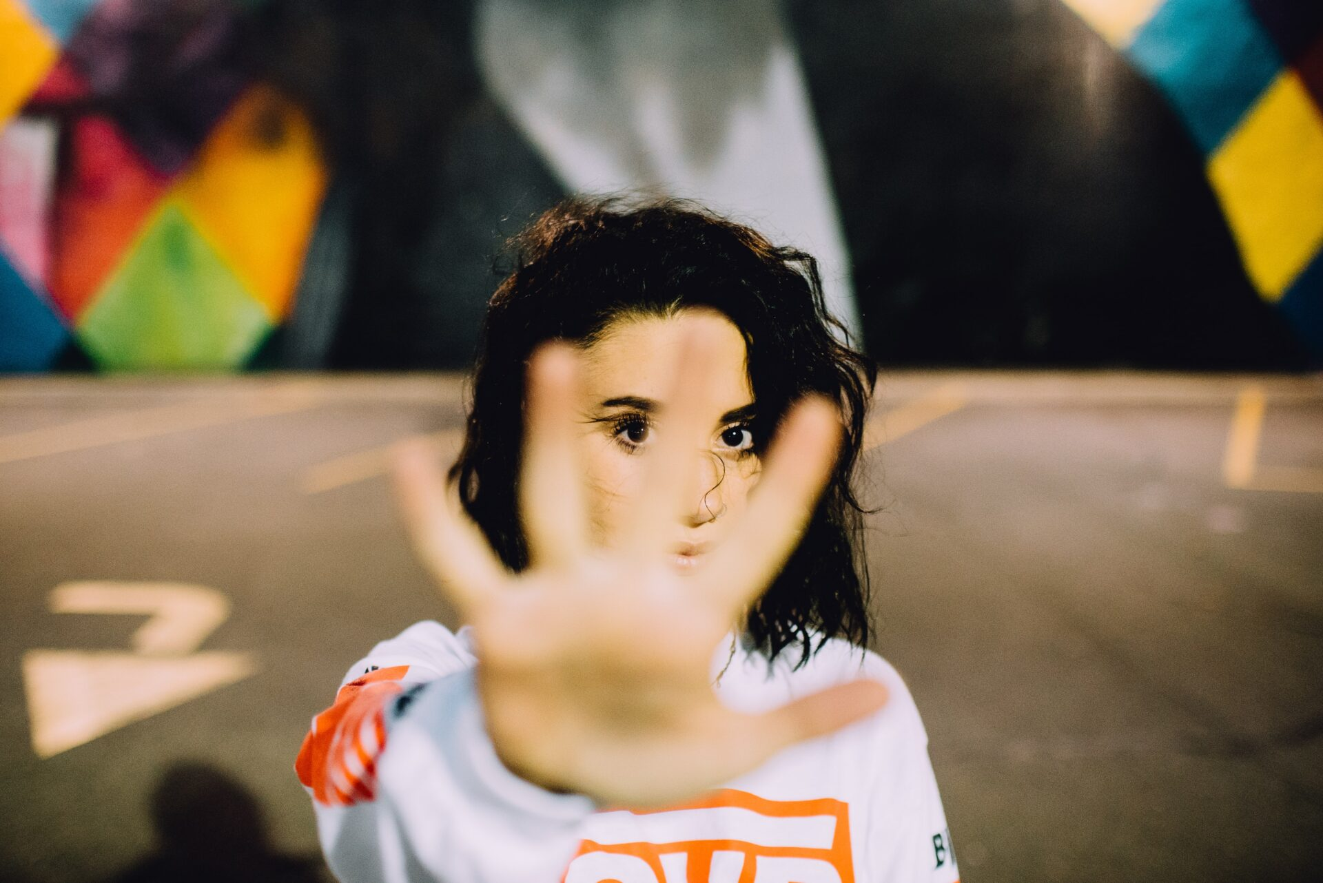 girl standing in front of a grafiti wall with her hand out in front of her face