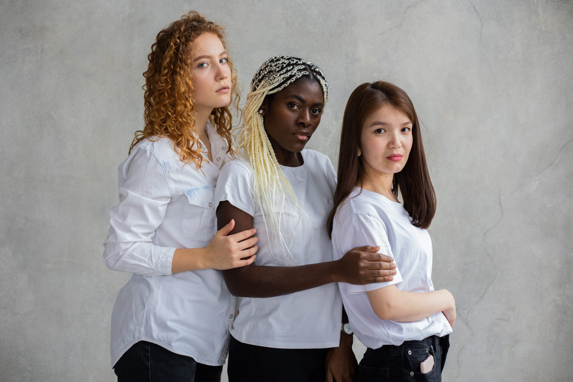 three women from different backgrounds and cultures, standing in a row