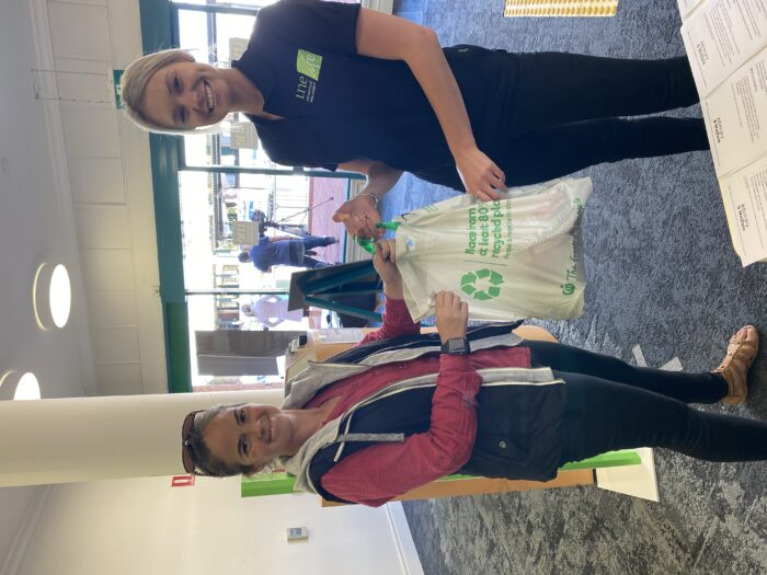 UNE Life Advocate handing a bag of groceries to a student at a CUC Centre