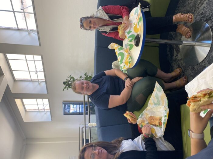 a group of happy students eating lunch and sitting at a CUC centre when meeting UNE Life Advocates in the Road